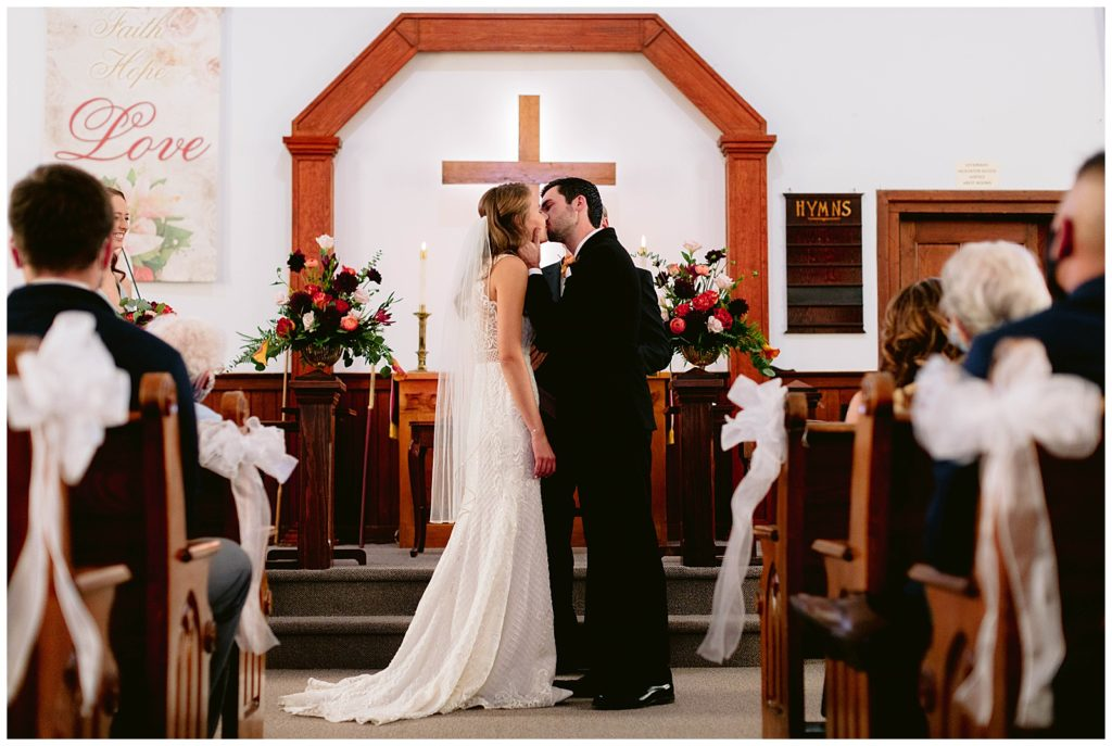 Bride and groom share their first kiss during their wedding ceremony. Photo is timeless, classic, and elegant.